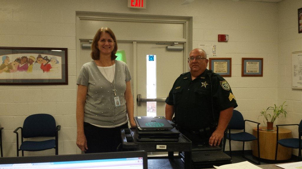 Westside's Assistant Principal Mrs. J. Camp accepts the 21 laptops from School Resource Sgt. Tim Ball