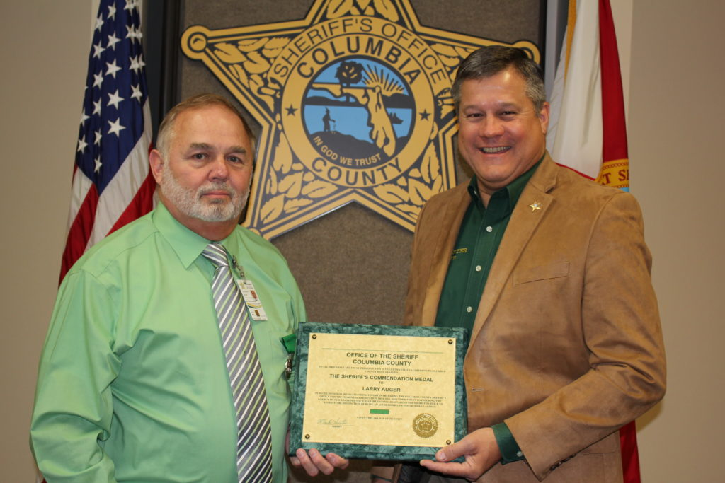 Larry Auger recieving award from Sheriff