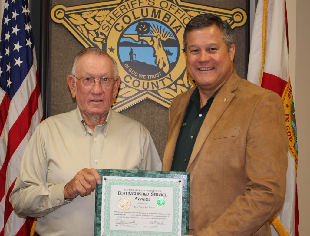 Sheriff giving plaque to Zimmie Petty